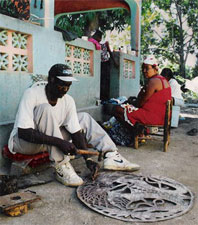 Haitian artist carving oil drum with hammer & chisel